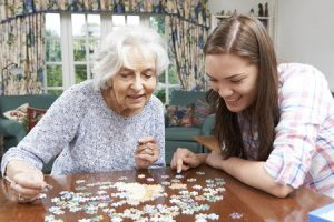 46634490 - teenage granddaughter helping grandmother with jigsaw puzzle